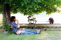Carpenter enjoying coffee in shade. Of tree royalty free stock photo
