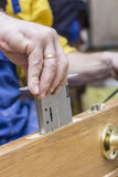Carpenter establishes the in a wooden door mortise lock. royalty free stock photography