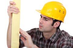 Carpenter examining plank Stock Photography