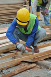Carpenter fabricating timber form work at the construction site Royalty Free Stock Photos