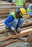 Carpenter fabricating timber form work at the construction site Stock Image