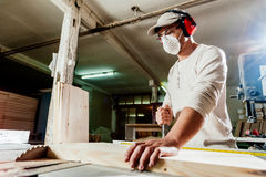 Carpenter in factory. Carpenter working with Industrial tool in wood factory wearing safety glasses and hearing protection Stock Image