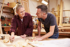 Carpenter With Female Apprentice Planing Wood In Workshop Stock Photography