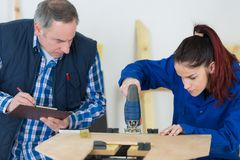Carpenter with female apprentice working on building site. Female stock photography