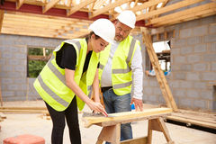 Carpenter With Female Apprentice Working On Building Site Stock Image