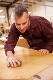 Carpenter Finishing Wood In Carpentry Workshop Royalty Free Stock Photo