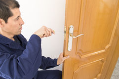 Carpenter fixing a lock in the door Stock Photos