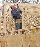 Carpenter framing gable end of house. With many roof trusses in background Royalty Free Stock Photos