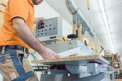 Carpenter in furniture factory pressing button on machine Stock Image