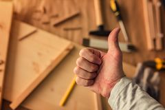 Carpenter is gesturing thumbs up. After being satisfied after completing woodwork project stock photography