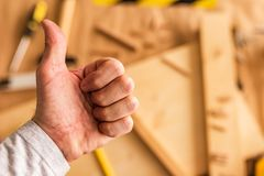 Carpenter is gesturing thumbs up. After being satisfied after completing woodwork project stock photos