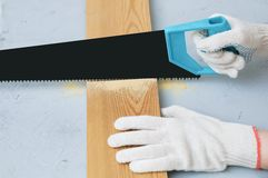 Carpenter in gloves is sawing a wooden board with a saw. stock images