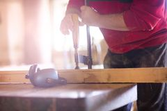 Carpenter gluing wooden planks Stock Images