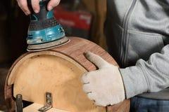 Carpenter grinding handmade wooden drum with sandpaper Stock Photos