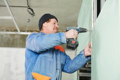 Carpenter with gypsum plasterboard and screwdriver Royalty Free Stock Images