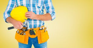 Carpenter with hammer against yellow background Royalty Free Stock Image