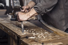 Carpenter with a hammer and chisel Royalty Free Stock Images
