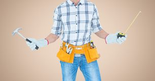 Carpenter with hammer and measuring tape against cream background. Digital composite of Carpenter with hammer and measuring tape against cream background Stock Photography