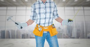 Carpenter with hammer and measuring tape against window Royalty Free Stock Photos