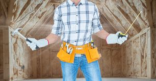 Carpenter with hammer and measuring tape in attic with flare Stock Images