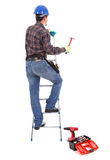 Carpenter with hammer on the stepladder. On the white background. Isolated on white royalty free stock photo
