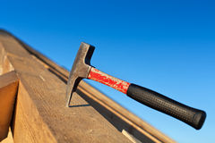 Carpenter hammer stuck into a wooden beam Royalty Free Stock Image