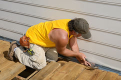 Carpenter Hammering. A carpenter hammering on a deck patio Royalty Free Stock Photos