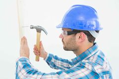 Carpenter hammering nail on wooden plank Stock Photography