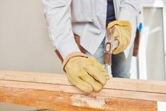 Carpenter hammering on wood Royalty Free Stock Photos
