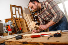 Carpenter hammering wood dowel Stock Image