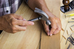 The carpenter hammers nail into. A plate Royalty Free Stock Photography