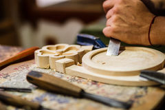 Carpenter hand carving wood with care Royalty Free Stock Photography