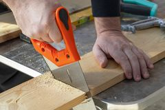 Carpenter hand with handsaw cutting wooden boards. stock image