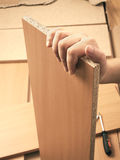 Carpenter hand holding plank and mounting brown Royalty Free Stock Photography