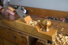 Carpenter hand holding wooden hand planer Stock Photo