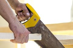 Carpenter hand with saw cutting wooden boards Royalty Free Stock Photography