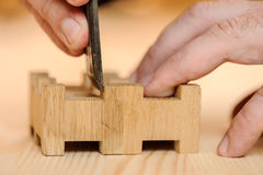 Carpenter hands cutting wood with chisel. Closeup royalty free stock images