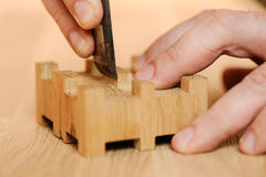 Carpenter hands cutting wood with chisel. Closeup royalty free stock photography