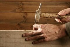 Carpenter hands with hammer wood and nail Stock Photos