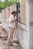Carpenter hands using electric drill on fence wood Stock Photo