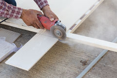 Carpenter hands using electric saw on wood. At construction site Royalty Free Stock Image
