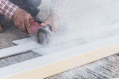 Carpenter hands using electric saw on wood. At construction site Royalty Free Stock Images