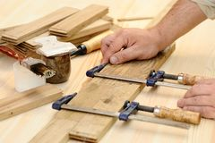 Carpenter hands at work with clamp. Closeup Stock Photo