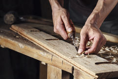 Carpenter hands working with a chisel and carving tools. Closeup of a carpenter hands working with a chisel and carving tools on wooden workbench royalty free stock photos