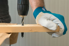 Carpenter handyman using electric drill. To make holes on plank on the woodwork workshop table Royalty Free Stock Photos