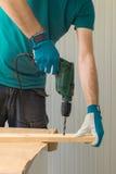 Carpenter handyman using electric drill Stock Photography