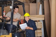 Carpenter Holding Clipboard By Colleague In. Senior carpenter holding clipboard by colleague sitting in forklift at workshop Royalty Free Stock Photos