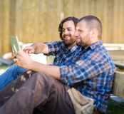 Carpenter Holding Digital Tablet While Coworker Royalty Free Stock Images