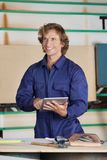 Carpenter Holding Digital Tablet While Looking Royalty Free Stock Photo