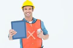 Carpenter holding digital tablet and mobile phone Stock Photo